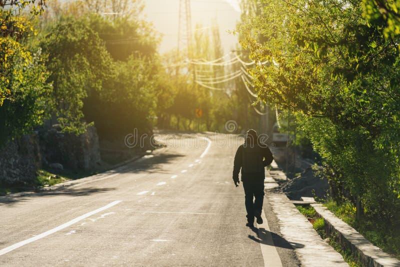 Een mens die met rugzak alleen op lege weg in de ochtend met helder zonlicht lopen stock afbeeldingen