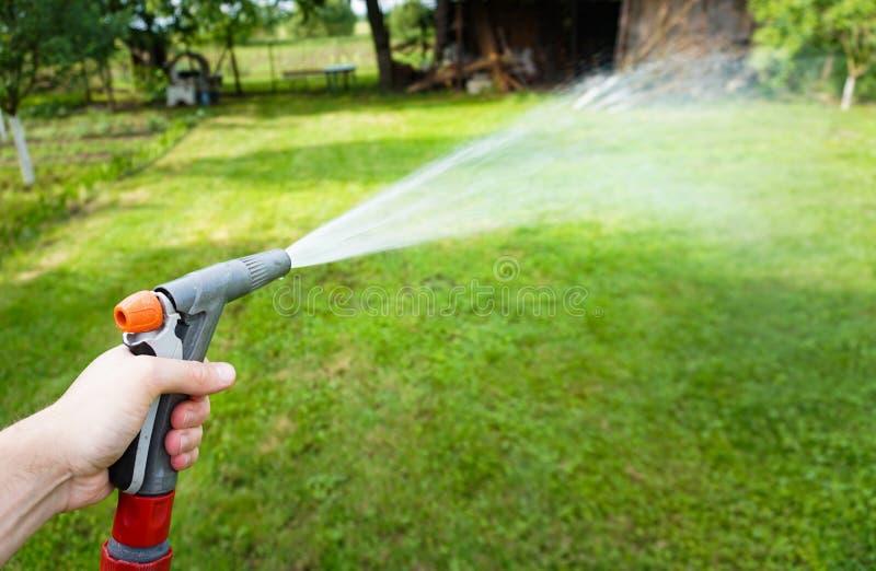 Een mens die met waterhuis het gazon water geven royalty-vrije stock afbeelding