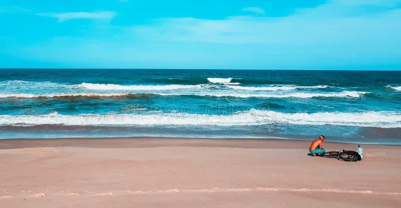 Een mens die met zijn fiets op het strand Fortaleza Ceara Brazilië rusten royalty-vrije stock foto's