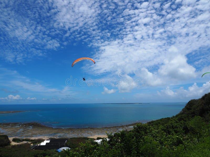 Een mens die op de mooie blauwe bewolkte mooie hemel met het overzees en de bergachtergrond vliegen, valscherm met een motor, par stock foto