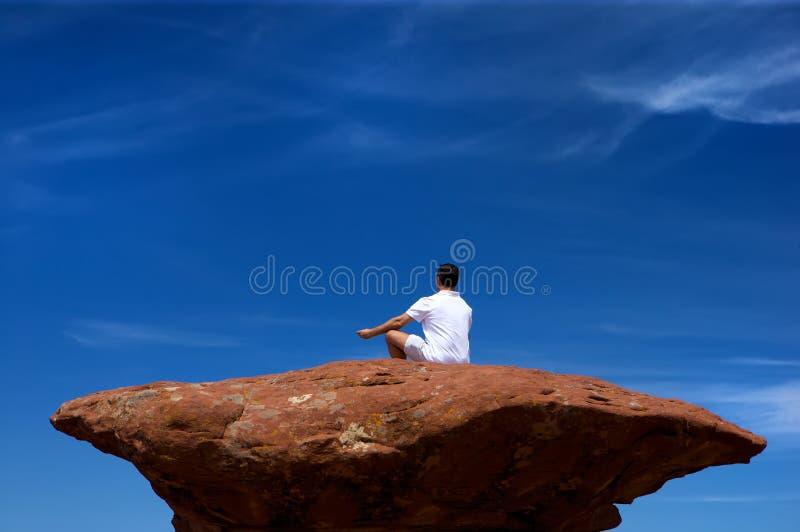 Een mens die op een hoge rots mediteert royalty-vrije stock afbeelding
