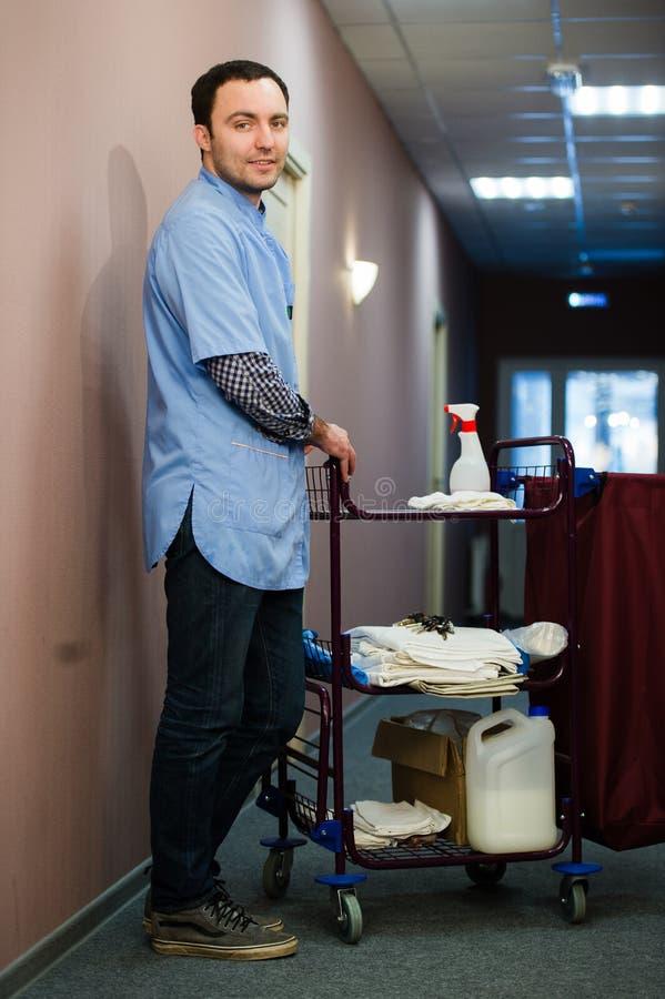Een mens die op het personeel is van de hotel schoonmakende bemanning glimlacht met een handdoekvacuüm tijdens het schoonmaken va royalty-vrije stock foto's