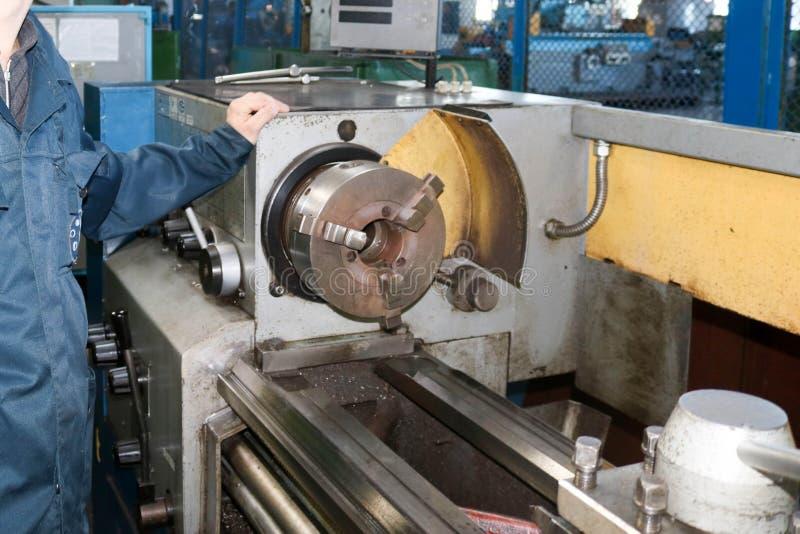 Een mens die in een robe, overall werken bevindt zich naast een industriële draaibank voor knipsel, die messen van metalen, hout  royalty-vrije stock afbeelding