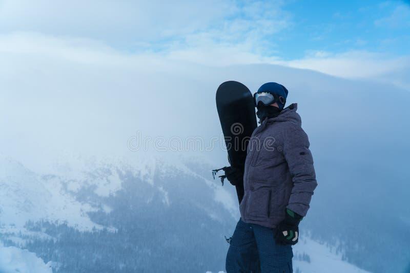 Een mens die een snowboard in hand houden Snowboarder in de bergen stock afbeeldingen