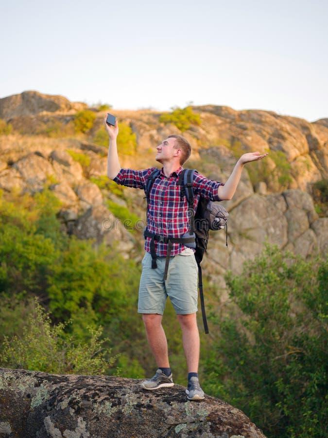 Een mens die een telefoon op een natuurlijke achtergrond proberen te roepen De toerist kan de vraag van ` t een telefoon Slecht v royalty-vrije stock afbeeldingen