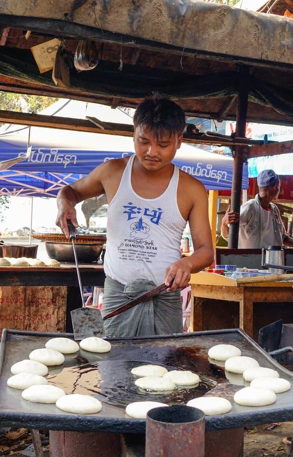Een mens die traditionele cakes koken bij de markt in Bagan, Myanmar stock foto