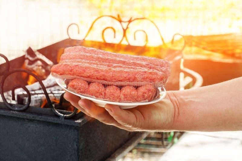 Een mens die verse chevapchichi op een witte schotel op de achtergrond van de brandbarbecue houden Cevapcici op de grill is Balka stock fotografie