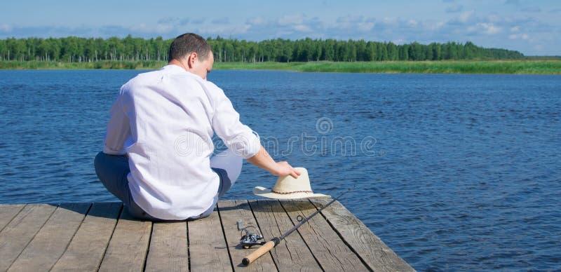 Een mens die in een wit overhemd, op de pijler zit, houdend een hoed, die naast een hengel voor visserij, tegen de blauwe hemel l stock fotografie
