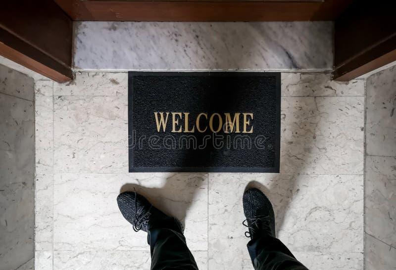 Een mens die zich bovenop een welkome vloermat bevinden voor een flatdeur royalty-vrije stock foto's