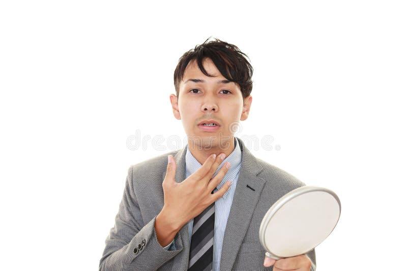Een mens die zich in een handspiegel bekijken stock foto's