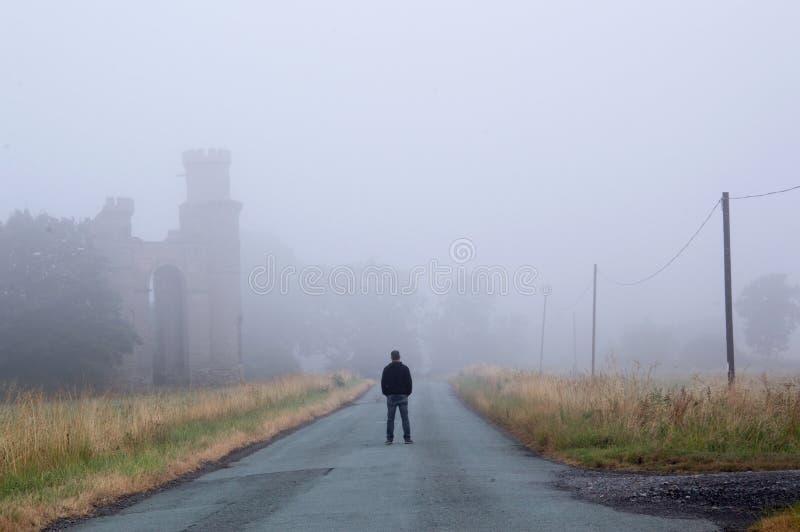 Een mens die zich in het midden van de weg naast een oud geruïneerd gebouw op een humeurige nevelige ochtend bevinden royalty-vrije stock foto's