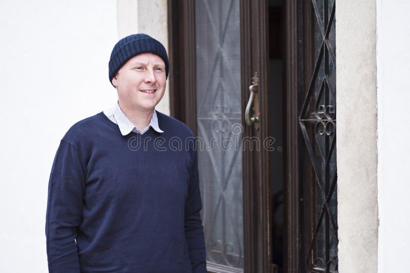 Een mens die zich naast bruine hoofddeur aan wit huis bevinden royalty-vrije stock foto