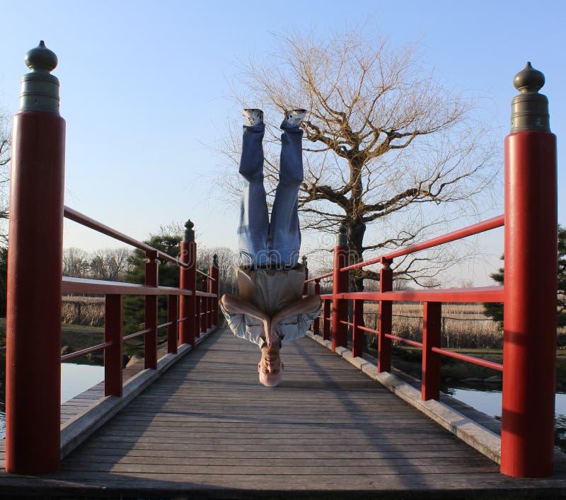 Een Mens die zich op zijn Hoofd op een Japanse Brug bevinden stock fotografie