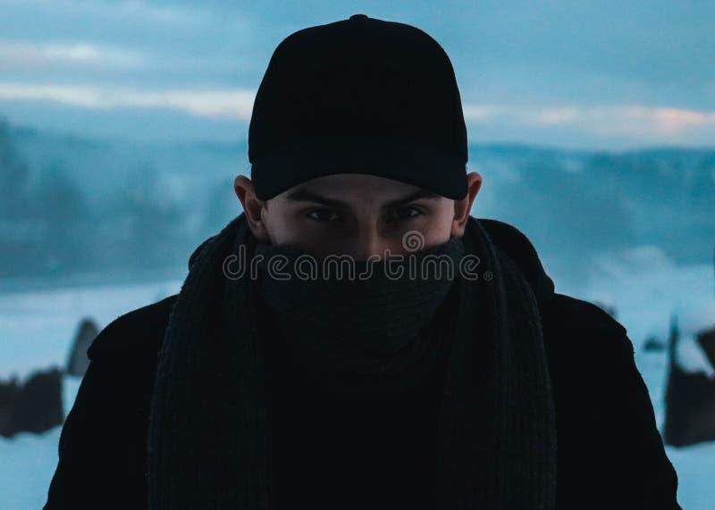 Een mens die zich voor een mooi die de winterlandschap bevinden met een sjaal wordt behandeld stock afbeeldingen