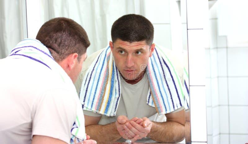 Een mens die zijn gezicht wast stock foto