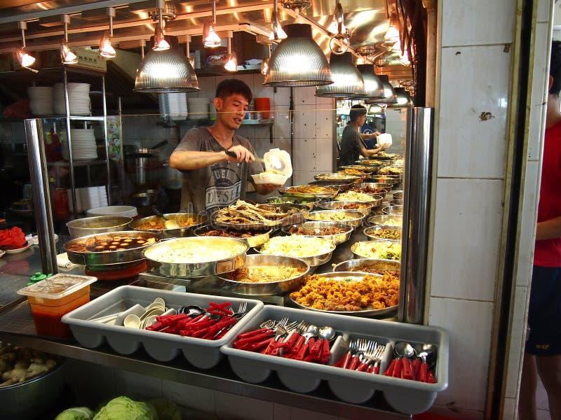Een mens dient voedsel voor een klant bij een venter in de stad van Tampines in Singapore royalty-vrije stock fotografie