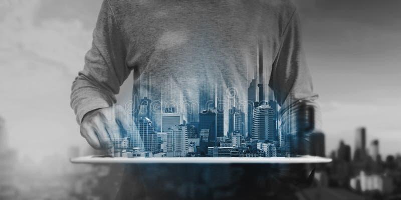 Een mens digitale tablet gebruiken, en modern gebouwenhologram die Onroerende goederenzaken en bouwtechnologieconcept stock foto