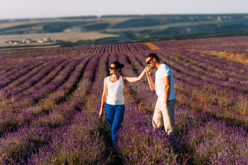 Een mens doet een voorstel aan een meisje op een bloemgebied Gelukkig paar op de lavendelgebieden Wittebroodswekenreis Een man ku stock foto's