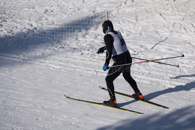 Een mens in donkere kleren, gaat in de afstand langs de weg in de sneeuw, op een de winterdag royalty-vrije stock foto's