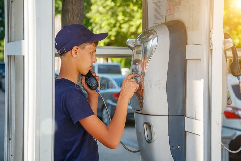 Een mens draait een telefoonaantal in een telefooncel royalty-vrije stock fotografie