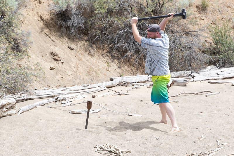 Een mens drijft een metaalstaak in het zandige strand met een sleehamer stock foto's