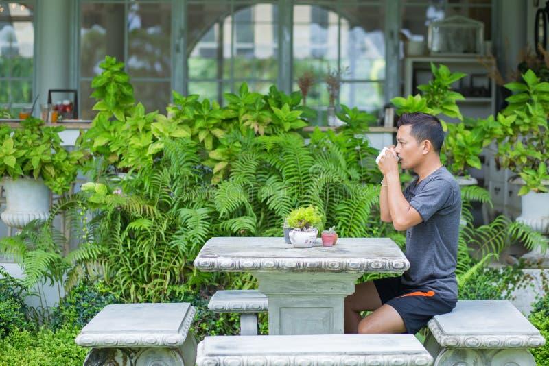 Een mens drinkt koffie in de ochtend bij koffiewinkel stock fotografie