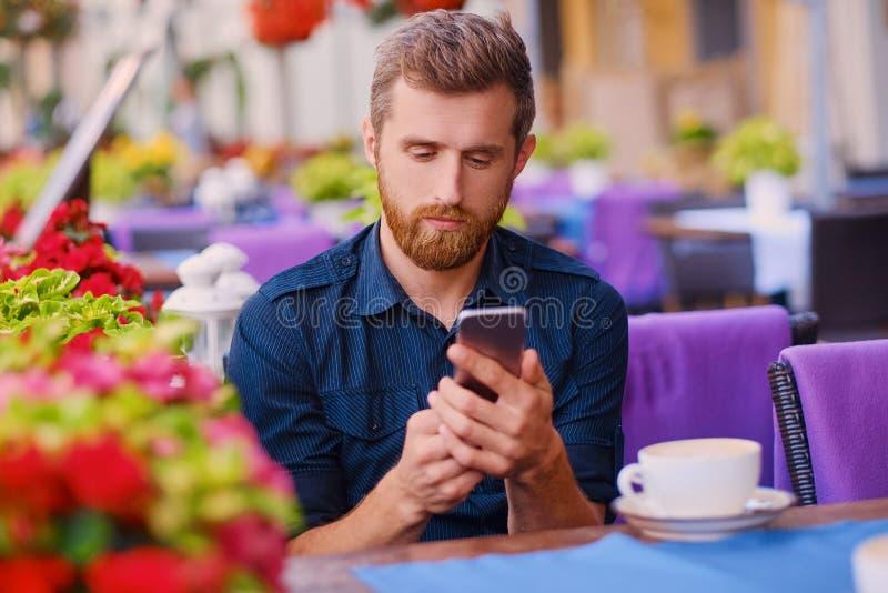 Een mens drinkt koffie en het gebruiken van een smartphone in een koffie royalty-vrije stock foto