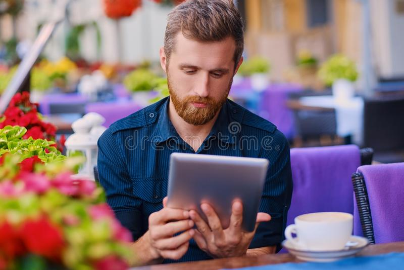 Een mens drinkt koffie en het gebruiken van een tabletpc in een koffie royalty-vrije stock fotografie