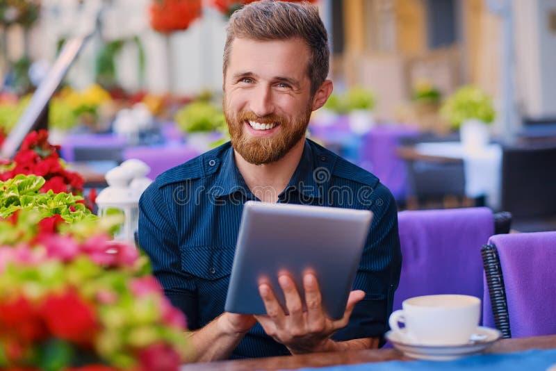 Een mens drinkt koffie en het gebruiken van een tabletpc in een koffie royalty-vrije stock afbeelding