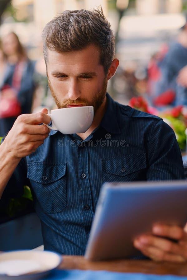 Een mens drinkt koffie en het gebruiken van een tabletpc in een koffie stock afbeeldingen