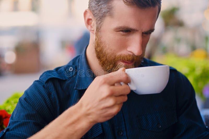 Een mens drinkt koffie in een koffie op een straat royalty-vrije stock foto's