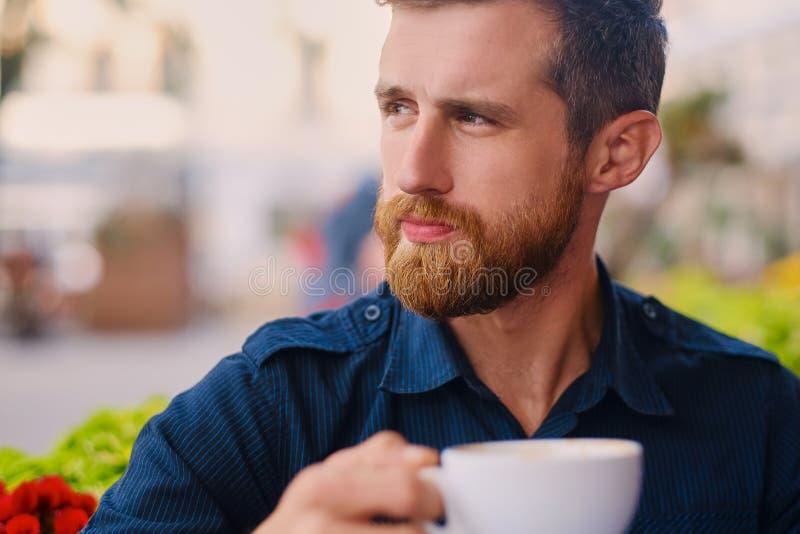 Een mens drinkt koffie in een koffie op een straat stock foto's