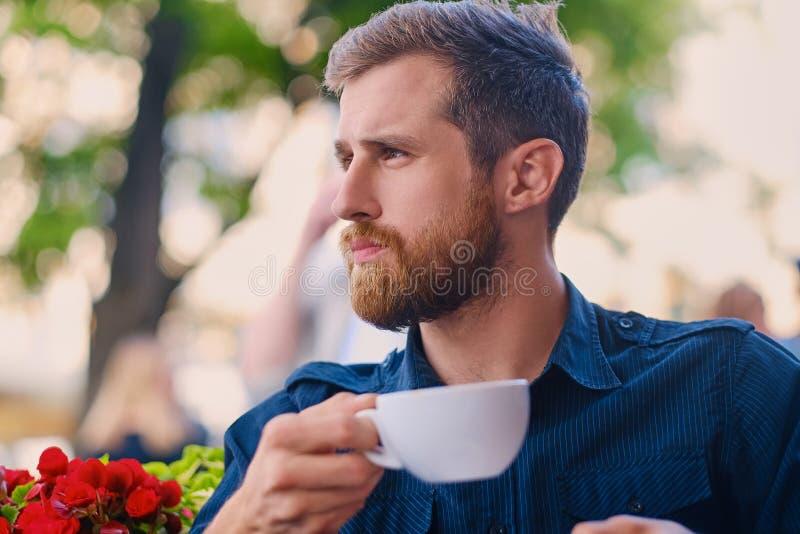 Een mens drinkt koffie in een koffie op een straat stock afbeelding