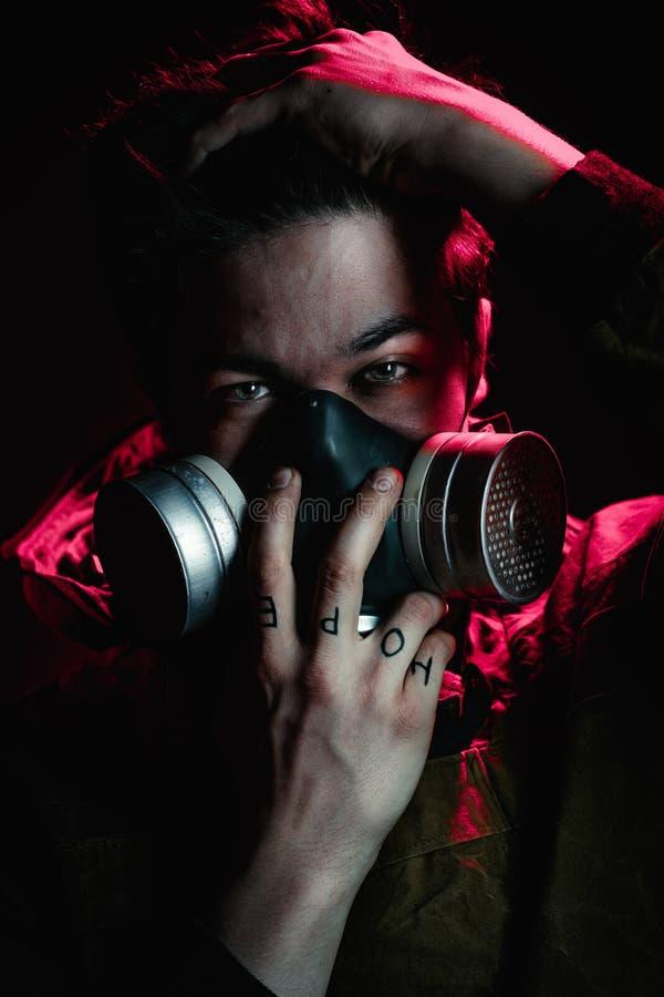 Een mens in een gasmasker op een zwarte achtergrond stock afbeelding