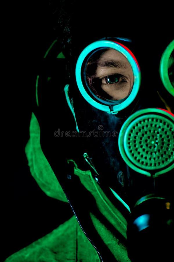 Een mens in een gasmasker op een zwarte achtergrond stock foto