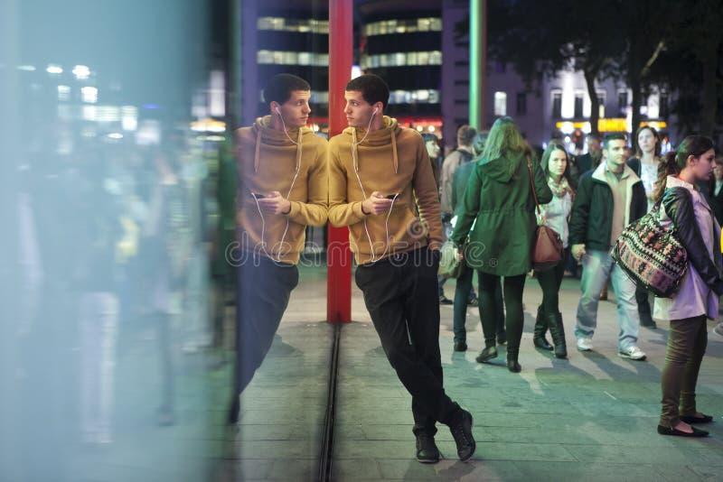 Een mens in een gele sweater status, die op een muur van glasm&m opslag leunen op Piccadilly-Circus Hij luistert aan muziek op ho royalty-vrije stock foto
