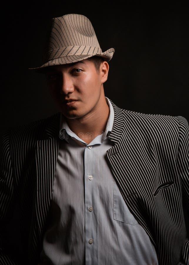 Een mens in een grijze hoed op zwarte achtergrond royalty-vrije stock afbeeldingen