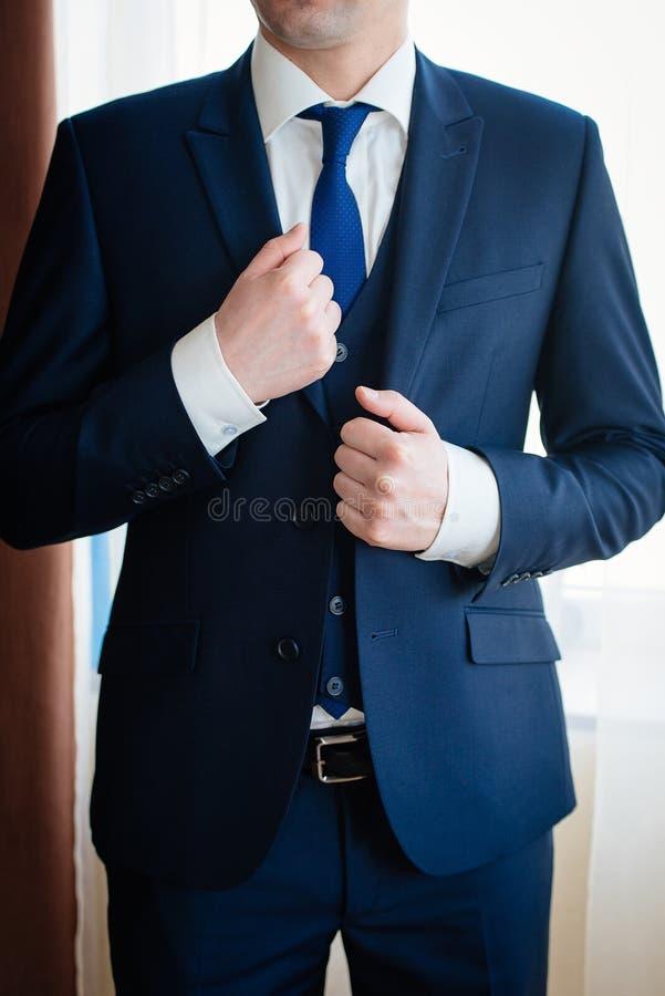 Een mens in een witte overhemd, een vest, een band en een klassiek blauw kostuum bevindt zich in binnenland royalty-vrije stock fotografie