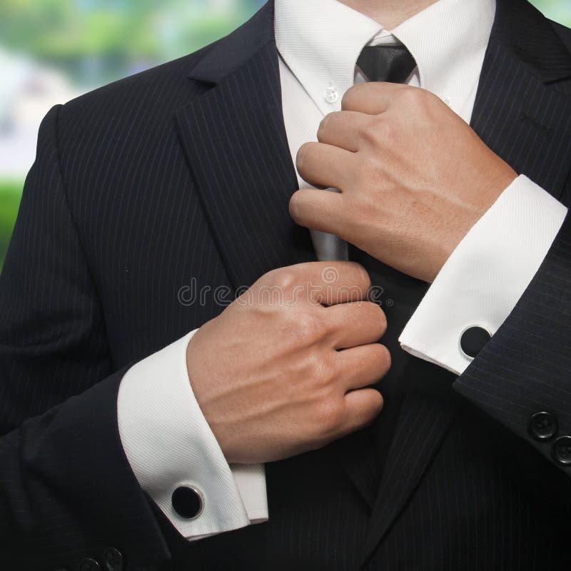 Een mens in een zwart kostuum maakt zijn band recht stock fotografie