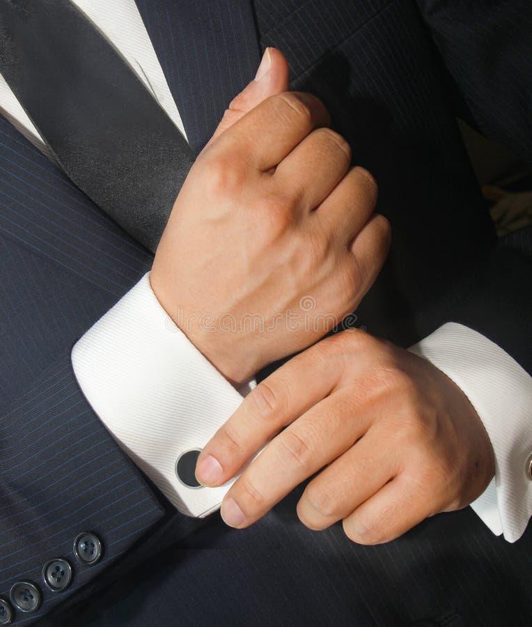 Een mens in een zwart kostuum maakt zijn cufflinks recht stock fotografie