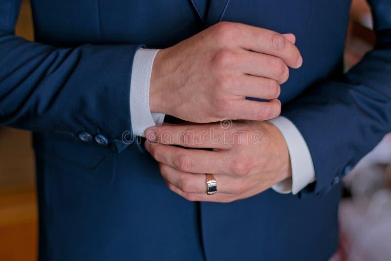 Een mens in een zwart kostuum maakt zijn cufflinks recht royalty-vrije stock fotografie
