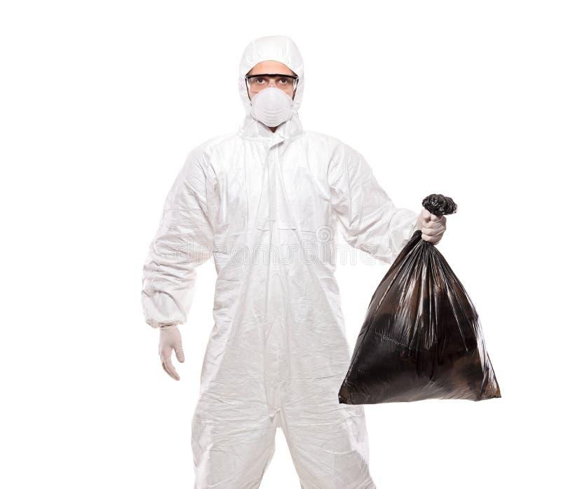 Een mens in eenvormige holding een zwarte vuilniszak stock fotografie