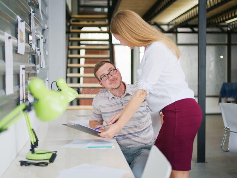Een mens en een meisje bespreken een businessplan in het bureau stock foto's