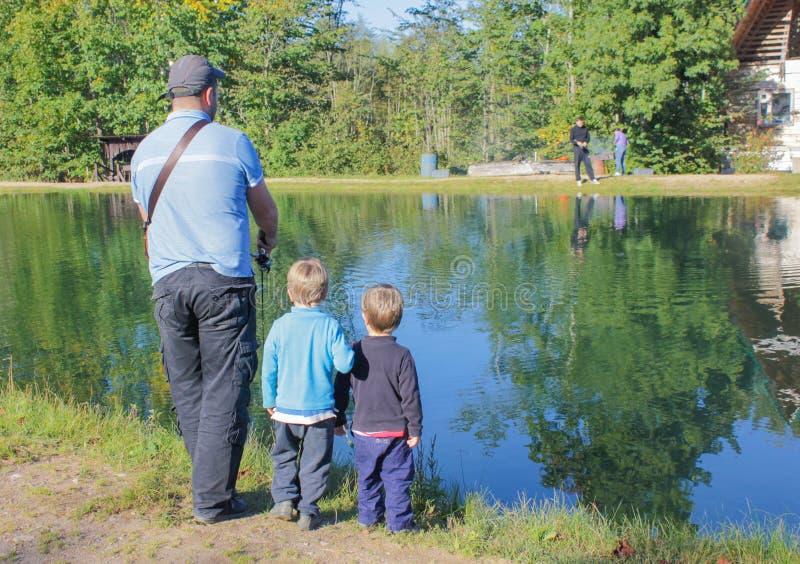 Een mens en twee kinderen visserij Vader en twee zonen die, tro vissen stock afbeeldingen