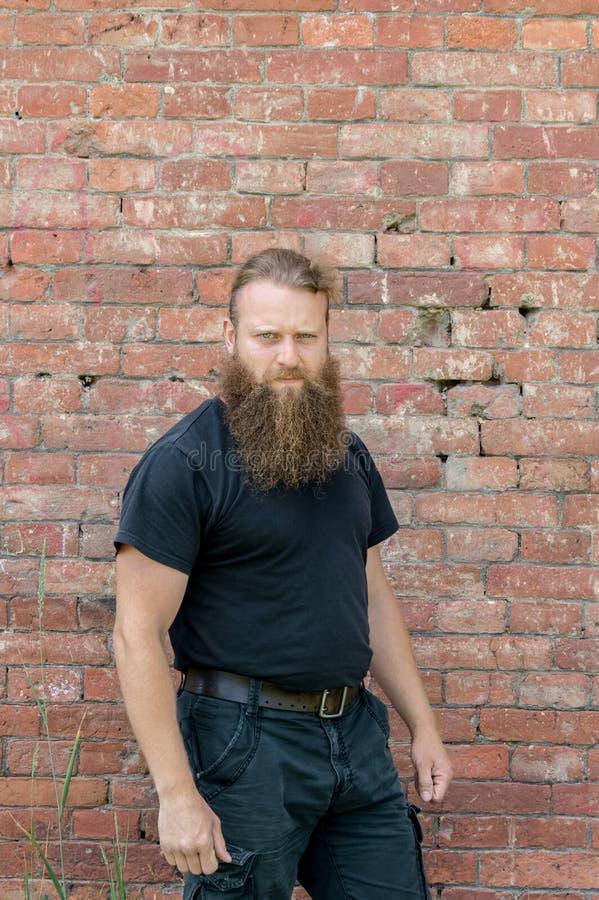 Een mens, een Europeaan met een baard, bevindt zich de helft van inschakelen de achtergrond van een rode muur van kerf royalty-vrije stock foto's