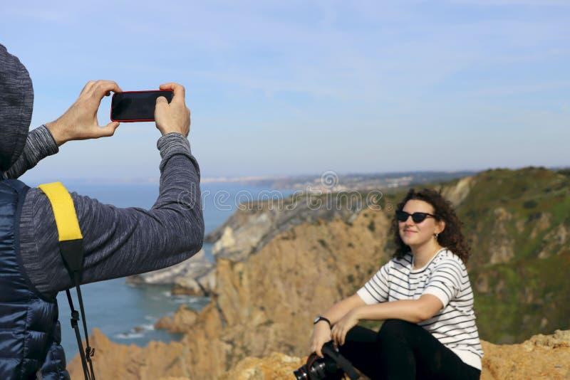 Een mens fotografeert een meisje met een camera op de telefoon royalty-vrije stock afbeelding