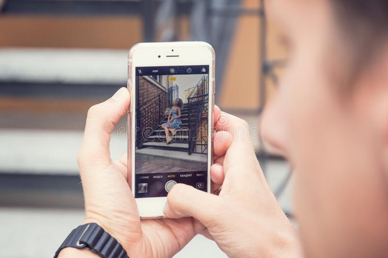 Een mens fotografeert op de telefoon zijn geliefd Vage trap op de achtergrond royalty-vrije stock afbeelding