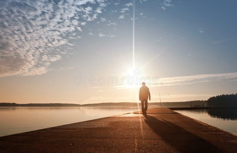Een mens gaat op de pijler in de zonsopgang royalty-vrije stock afbeelding