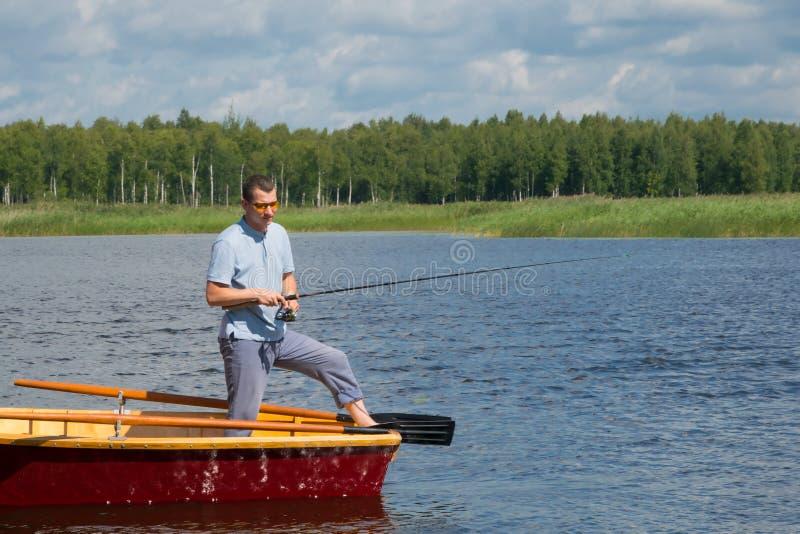 Een mens in gele glazen, in een boot met roeispanen, in het centrum van het meer, houdt een hengel om een grote vis te vangen, is stock afbeelding