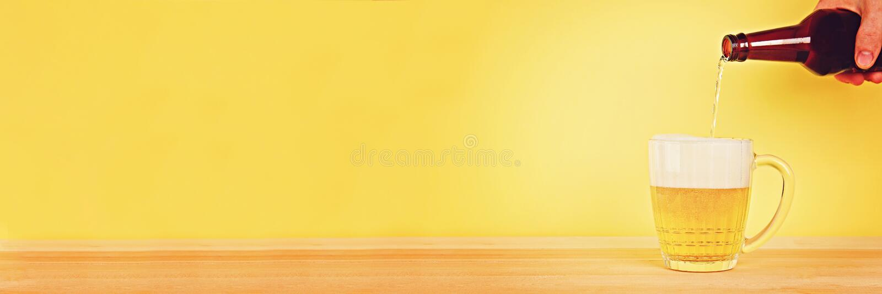 Een mens giet bier in een mok van een fles op een gele achtergrond op een houten lijst De ruimte van het exemplaar stock fotografie